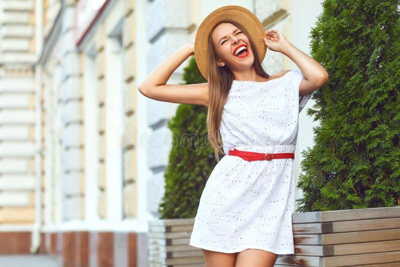 A menina em um chapéu e em um vestido está rindo em uma rua da cidade imagem de stock royalty free