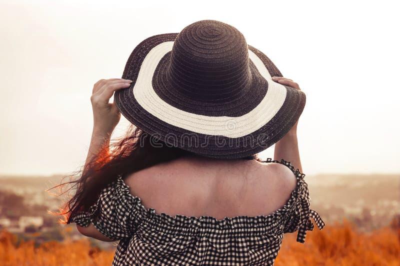 A menina em um chapéu olha o por do sol fotos de stock royalty free