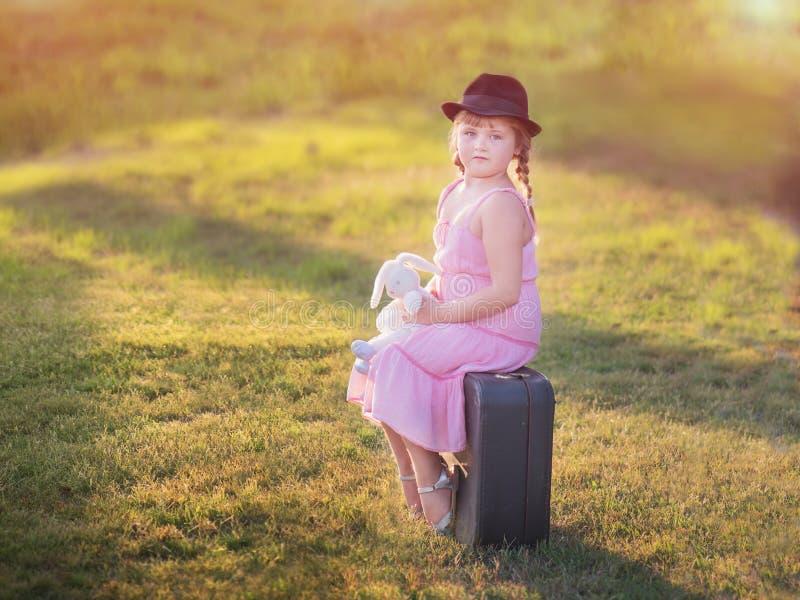 A menina em um chapéu senta-se em uma mala de viagem fotos de stock