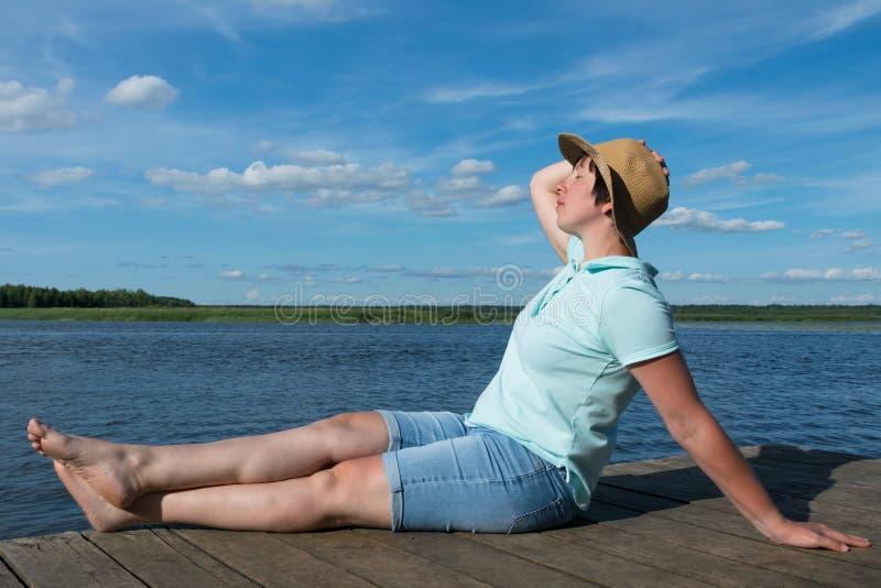 A menina em um chapéu toma sol em um cais pelo lago em um dia ensolarado quente imagens de stock royalty free