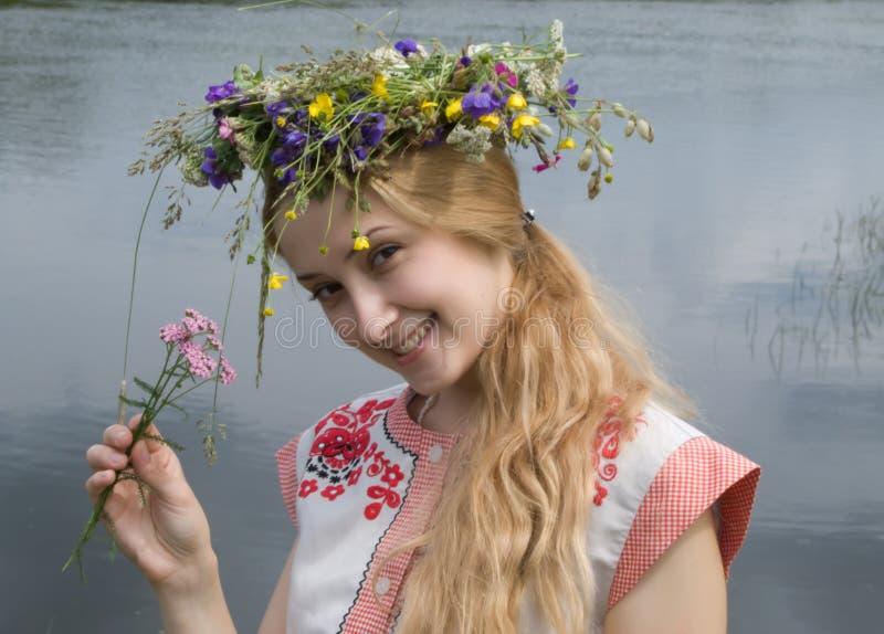 Menina em um chaplet das flores do prado fotos de stock royalty free