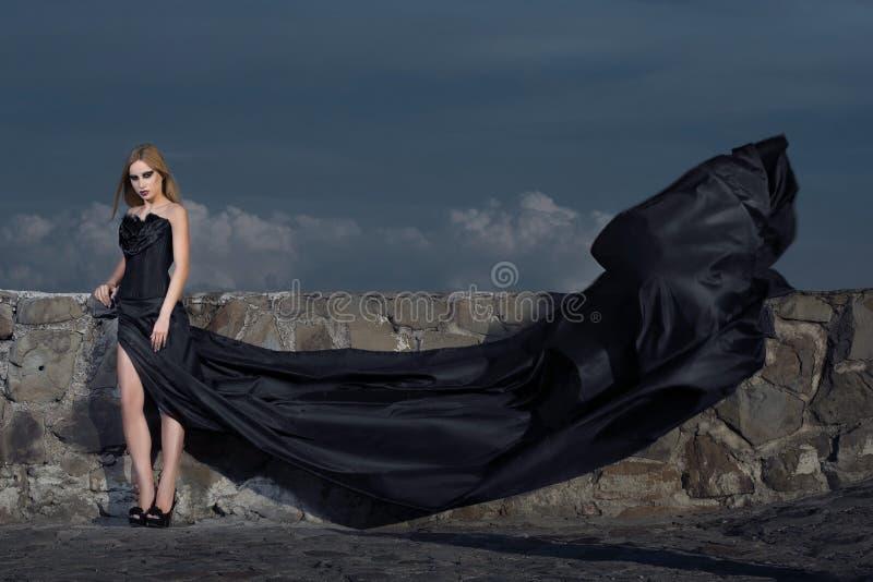 Menina em um espartilho com um trem longo na parede foto de stock royalty free