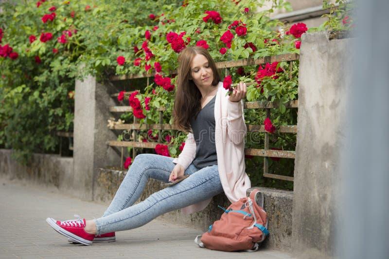 Menina em um fundo de flores encaracolados na cerca imagem de stock royalty free