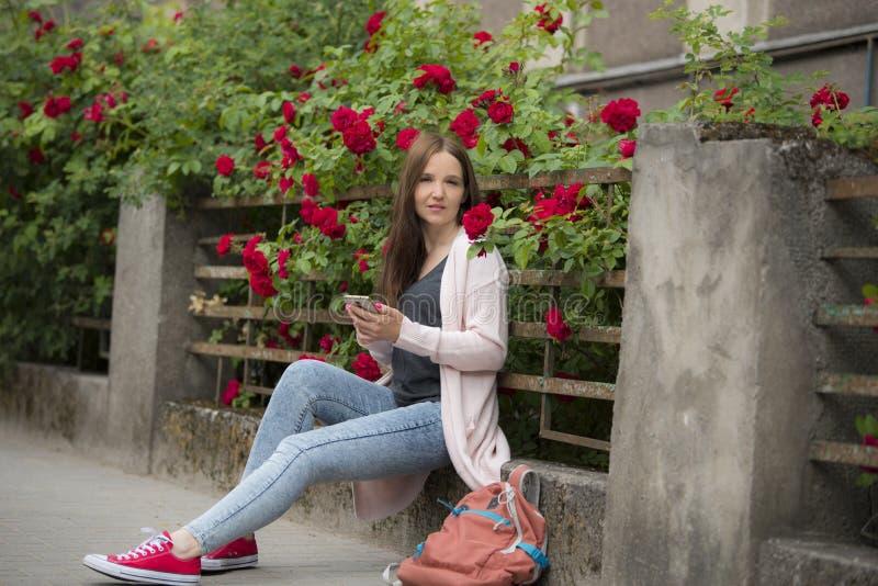Menina em um fundo de flores encaracolados na cerca foto de stock