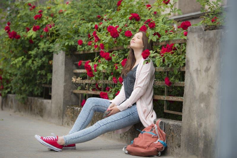 Menina em um fundo de flores encaracolados na cerca foto de stock royalty free