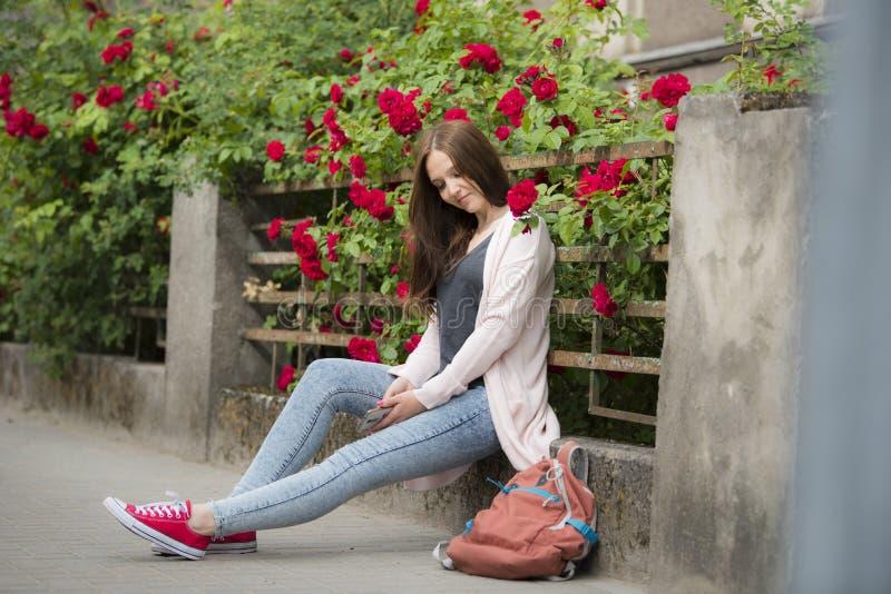Menina em um fundo de flores encaracolados na cerca fotografia de stock royalty free