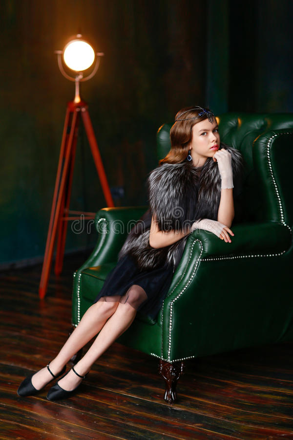 Menina em um Gatsby-estilo que senta-se em uma poltrona luxuoso nas luvas imagem de stock