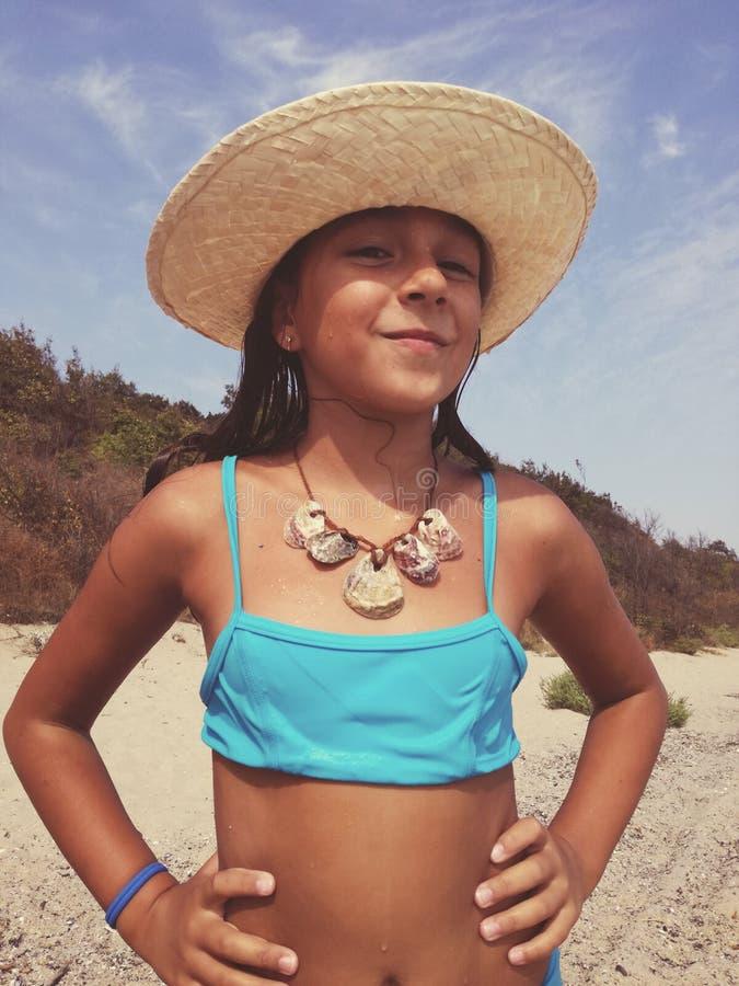 A menina em um maiô na praia veste uma colar de s imagens de stock royalty free