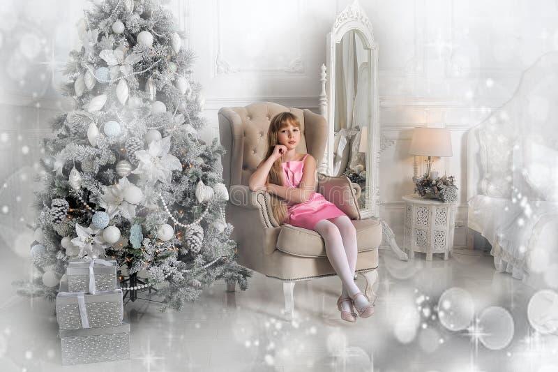 Menina em um pálido - vestido cor-de-rosa que senta-se em uma cadeira na árvore de Natal imagem de stock
