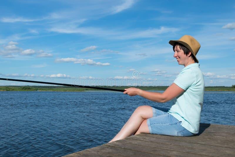 Menina em um peixe das capturas do chapéu no rio que senta-se no cais imagens de stock royalty free