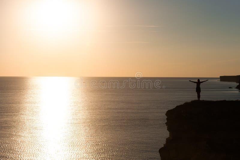 Menina em um penhasco acima do mar no por do sol fotografia de stock