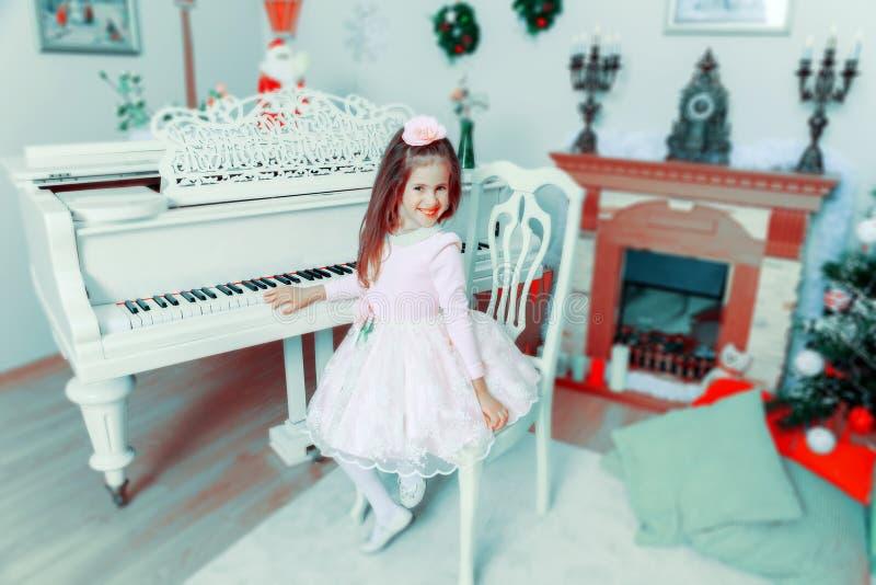 Menina em um piano de cauda branco fotografia de stock royalty free