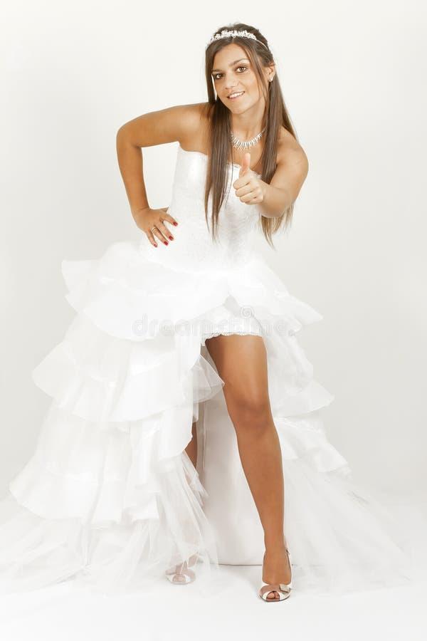 Menina em um polegar da mostra do vestido de casamento foto de stock