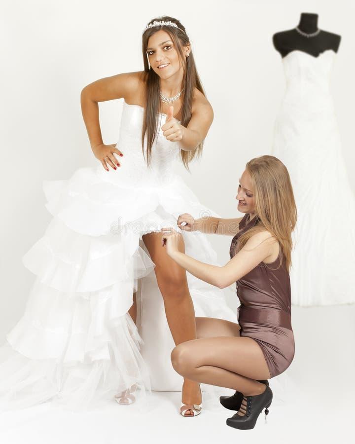 Menina em um polegar da mostra do vestido de casamento imagem de stock