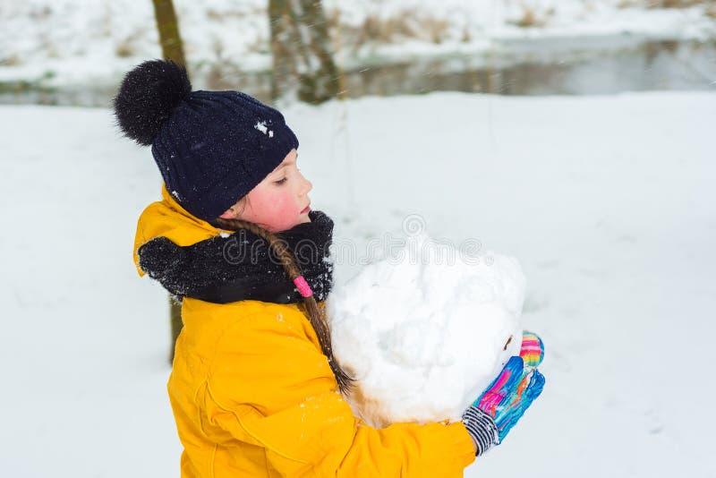 A menina em um revestimento amarelo e em um chapéu do inverno está levando uma grande bola de neve a menina faz um boneco de neve imagem de stock royalty free