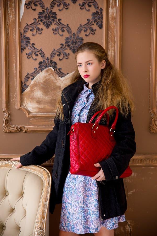 A menina em um revestimento com um saco vermelho imagens de stock royalty free