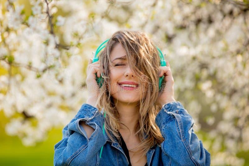 Menina em um revestimento da sarja de Nimes e suportes dos fones de ouvido perto de uma árvore de florescência foto de stock