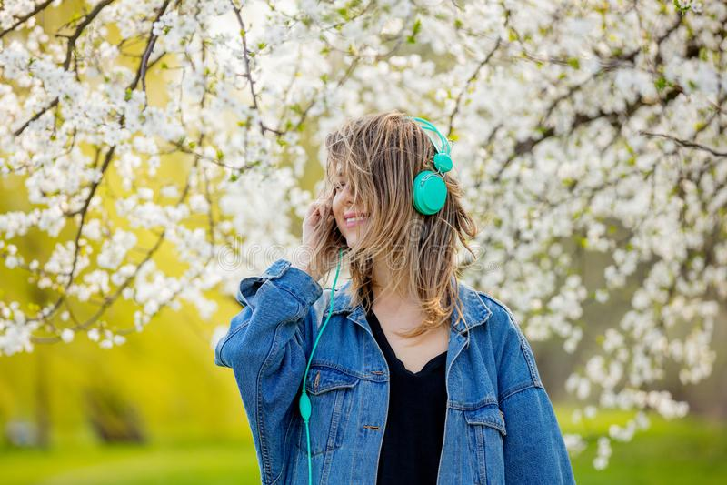 Menina em um revestimento da sarja de Nimes e suportes dos fones de ouvido perto de uma árvore de florescência imagens de stock