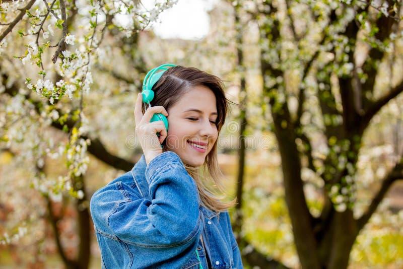 Menina em um revestimento da sarja de Nimes e suportes dos fones de ouvido perto de uma árvore de florescência foto de stock royalty free