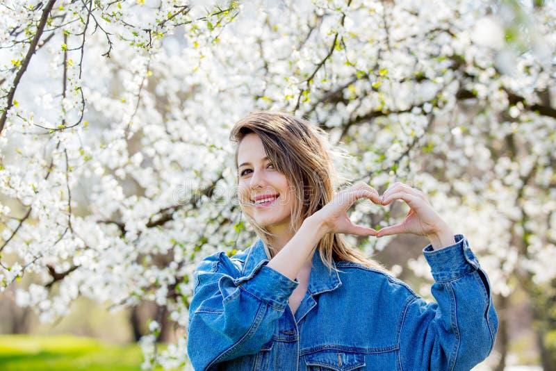 A menina em um revestimento da sarja de Nimes está perto de um sinal de florescência da mão do coração da árvore e da mostra fotografia de stock royalty free