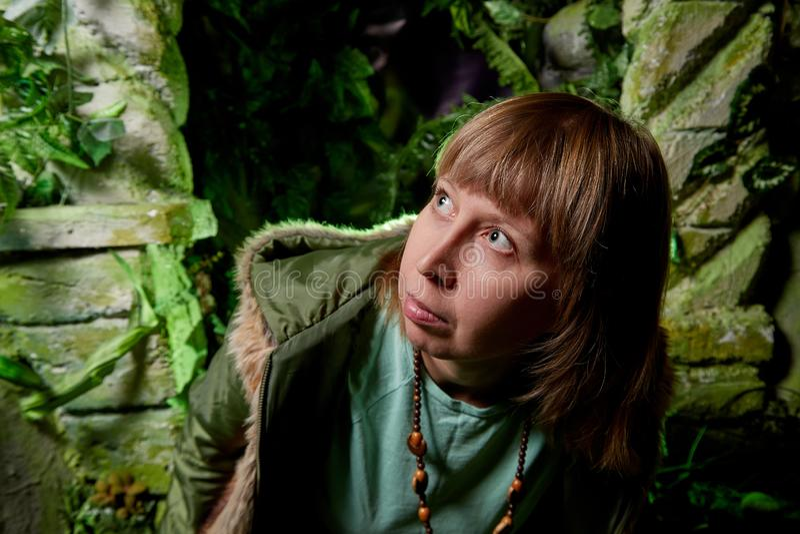 Menina em um revestimento verde com cabelo louro perto de uma rocha artificial com uma gruta Sessão fotográfica fabulosa no estúd fotos de stock royalty free