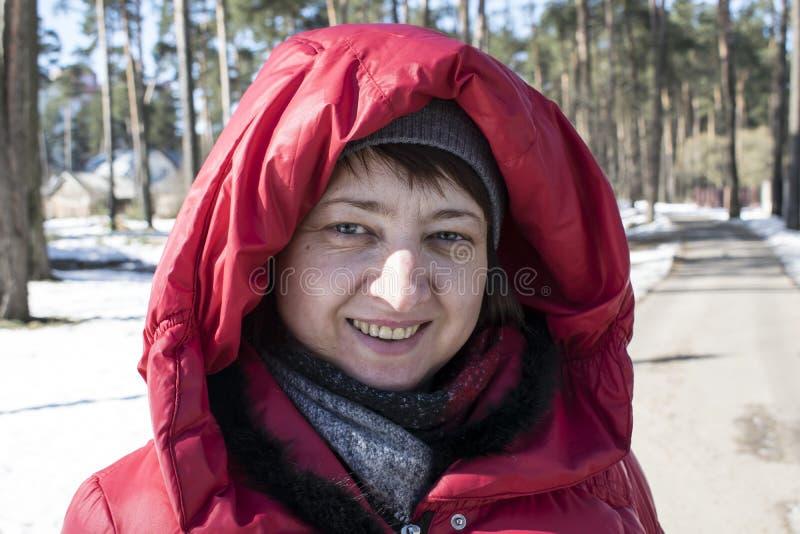 Menina em um revestimento vermelho exterior no inverno no parque fotos de stock