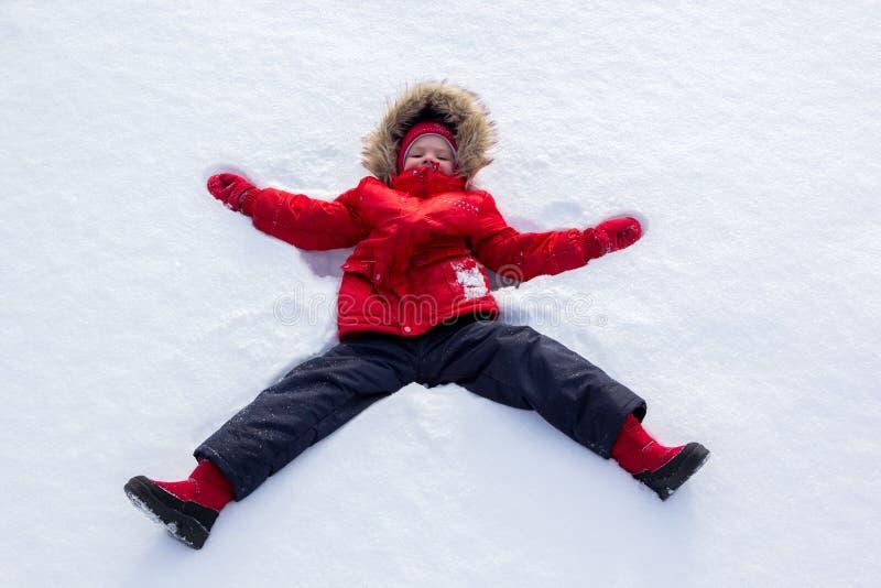 A menina em um revestimento vermelho faz o anjo da neve foto de stock royalty free