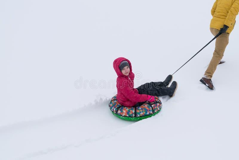 Menina em um revestimento vermelho que está sendo continuado um trenó redondo inflável na neve fotos de stock royalty free