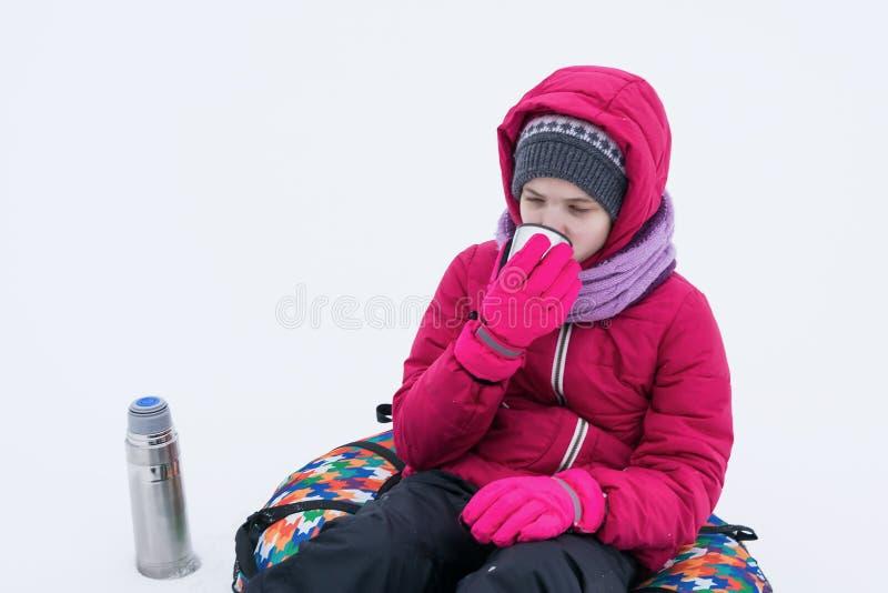 A menina em um revestimento vermelho senta-se na neve e bebe-se o chá morno de uma garrafa térmica imagens de stock