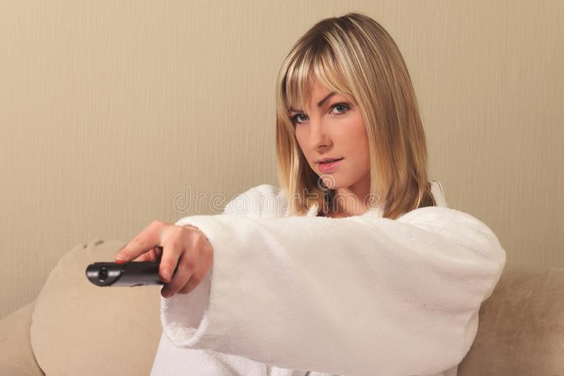 Menina em um roupão com o controlo a distância da tevê foto de stock
