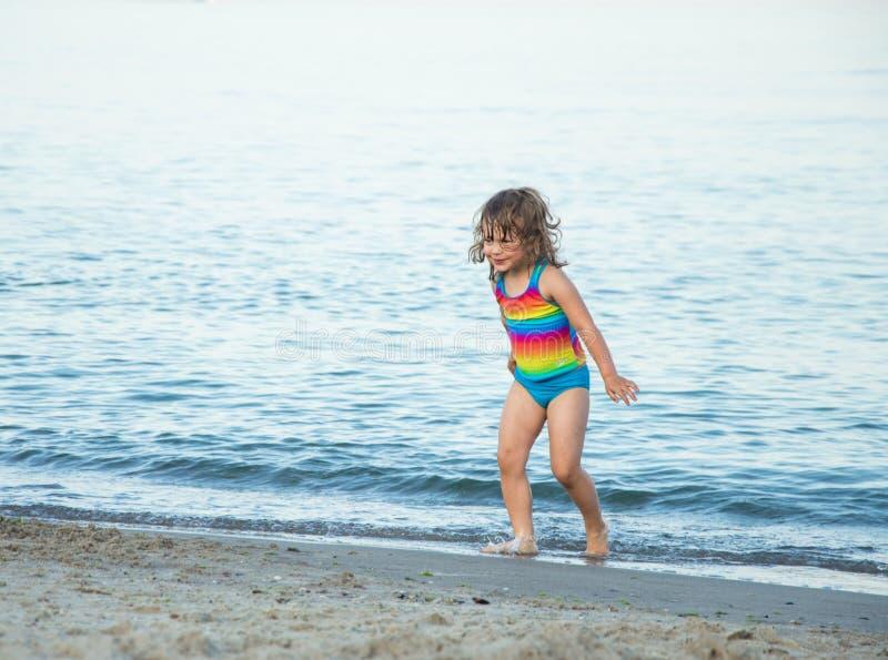 A menina em um roupa de banho colorido corre fora do mar imagens de stock royalty free