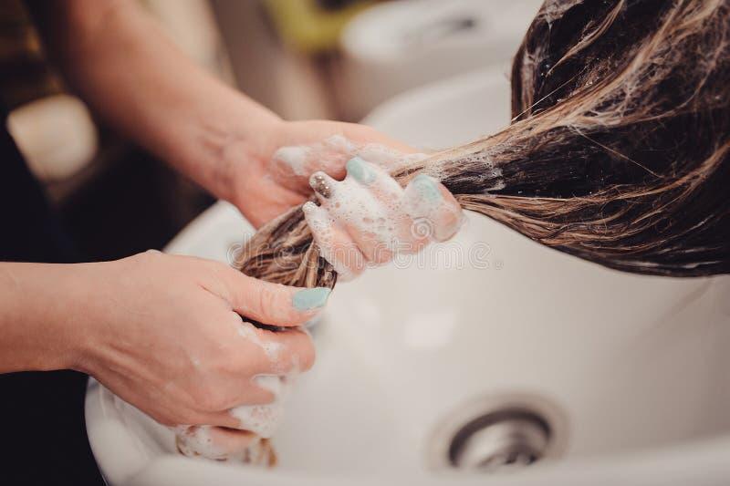Menina em um salão de beleza de beleza lave seu cabelo, cuidados capilares, saúde fotos de stock royalty free