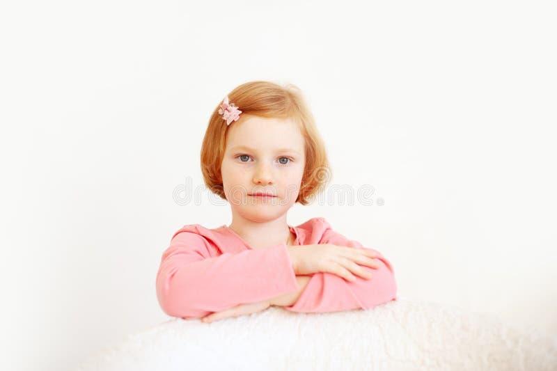Menina em um t-shirt cor-de-rosa e curva em seu cabelo no fundo branco imagem de stock royalty free