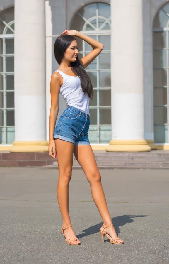 Menina em um t-shirt e short na frente de uma construção com colunas fotografia de stock royalty free