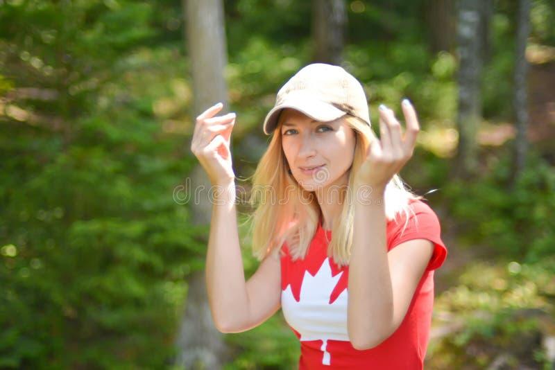 Menina em um t-shirt vermelho com um símbolo da folha de bordo de Canadá fotografia de stock