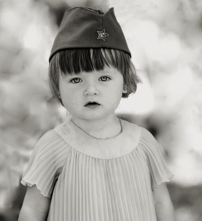 Menina em um tampão do ` s do soldado foto de stock