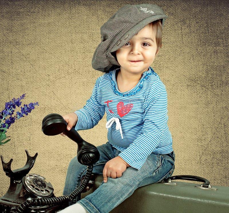 A menina em um tampão senta-se em uma mala de viagem foto de stock royalty free