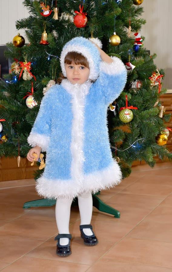 A menina em um terno da donzela da neve senta-se sobre um YE novo imagem de stock
