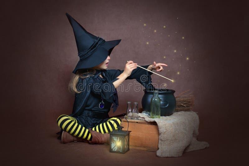 Menina em um traje da bruxa que faz a poção mágica foto de stock