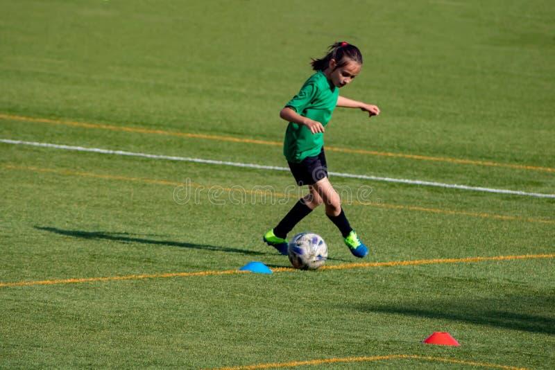 Menina em um treinamento do futebol fotografia de stock