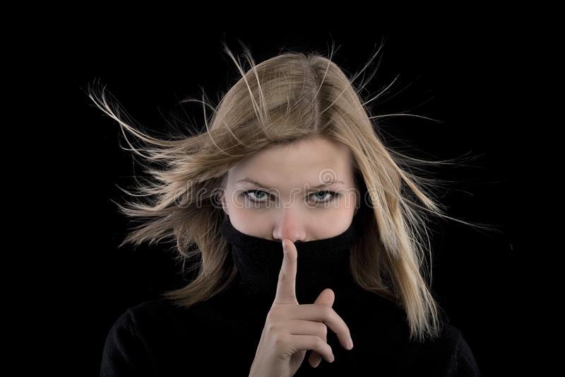 Menina em um turtleneck preto que faz um gesto do hush imagem de stock