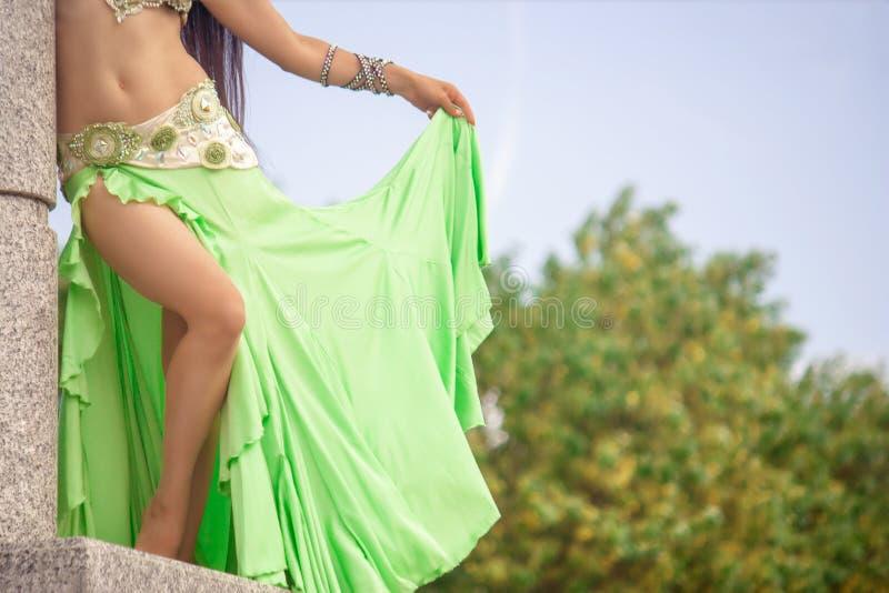 Menina em um verde, vestido do cal para poses da dan?a de barriga em uma coluna de m?rmore imagens de stock royalty free