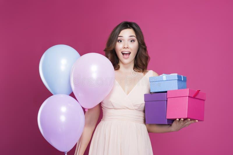 A menina em um vestido, é surpreendida e guarda presentes à disposição, em um fundo cor-de-rosa fotografia de stock