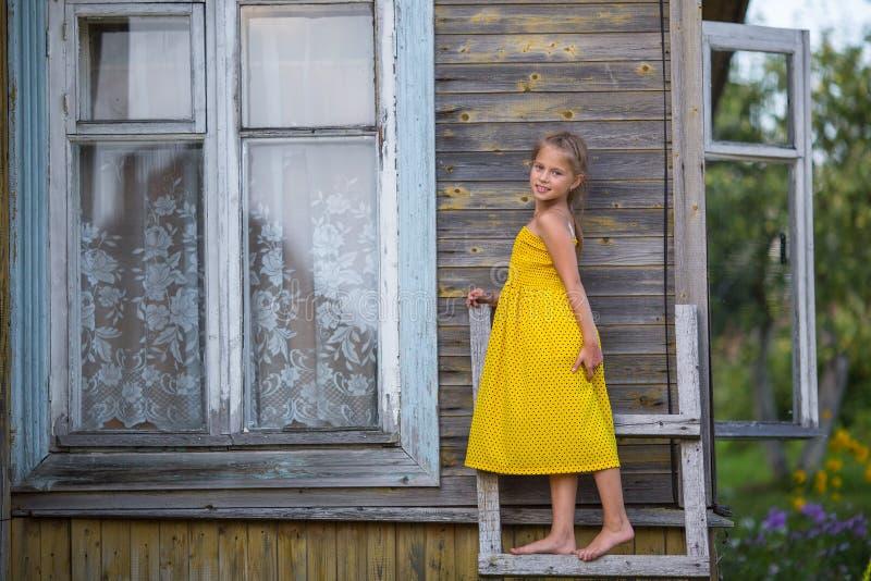 Menina em um vestido amarelo que está em uma escada de madeira perto da casa da quinta verão imagem de stock royalty free