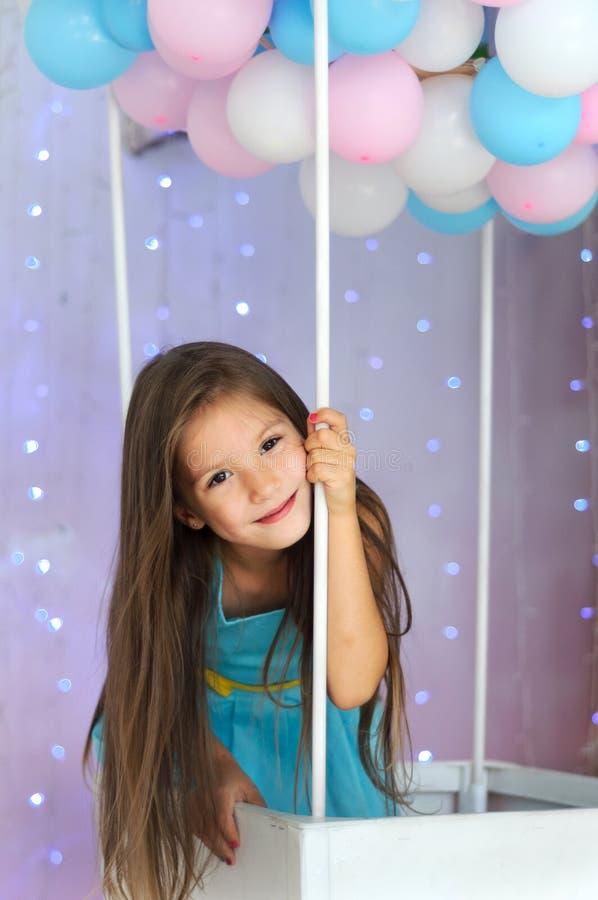 Menina em um vestido azul na cesta de um balão de ar quente imagens de stock royalty free