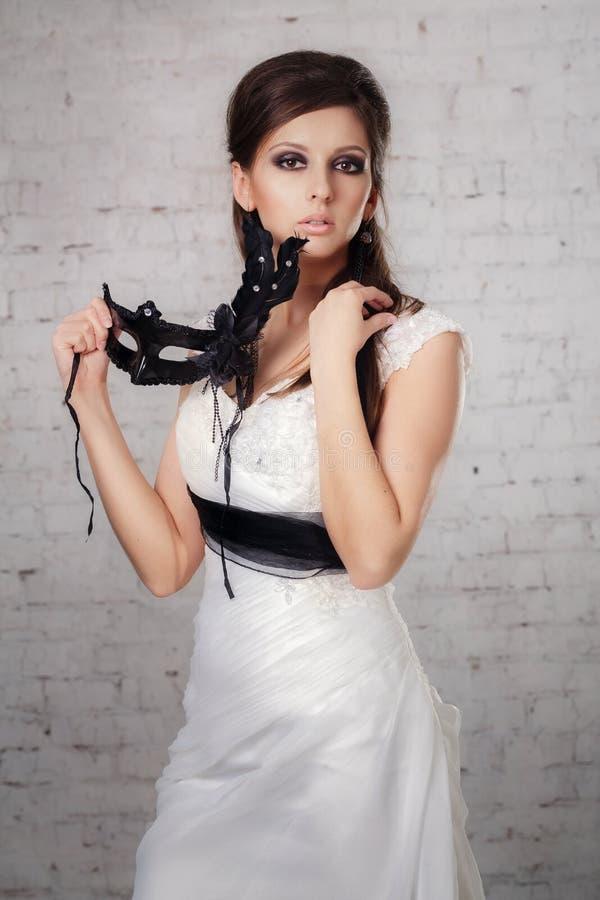 Menina em um vestido branco com uma máscara preta foto de stock