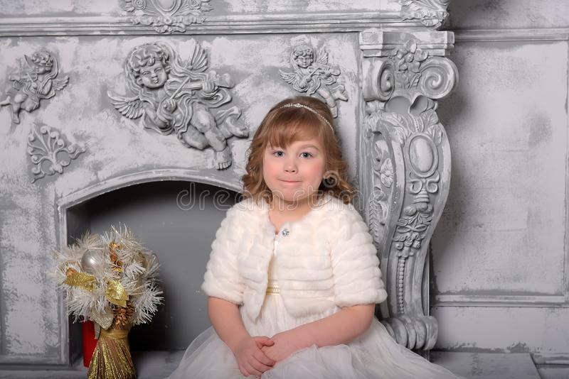 Menina em um vestido branco e em um casaco de pele pela chamin? velha no interior imagens de stock