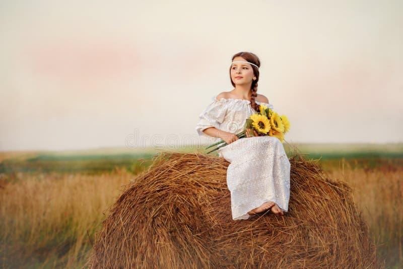 A menina em um vestido branco no campo senta-se no verão em um monte de feno fotos de stock royalty free