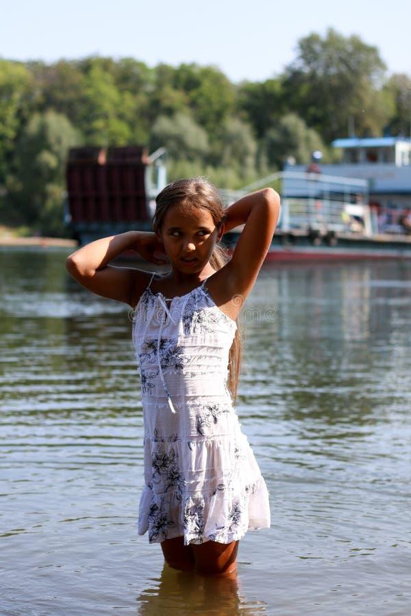 Menina em um vestido branco que está no rio imagens de stock