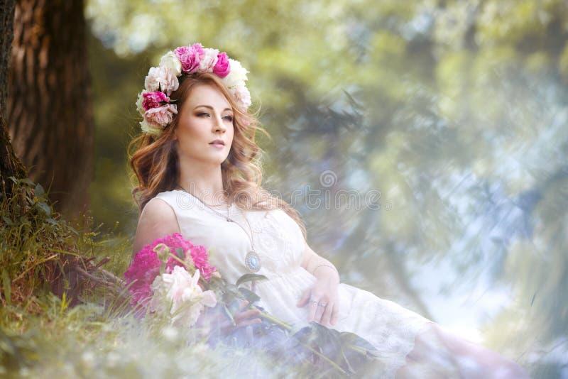 Menina em um vestido brilhante e em uma grinalda dos peons que descansam no prado imagens de stock royalty free